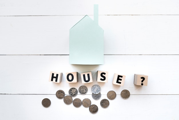 Modelo de casa de papel azul pequeño con bloques de madera de letras y monedas en mesa de madera blanca