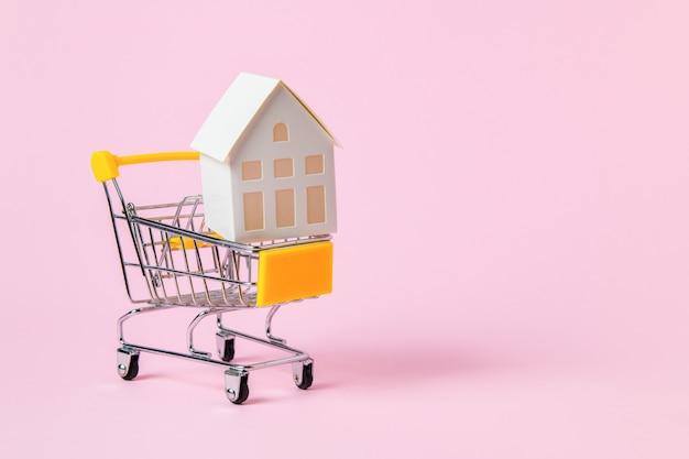Modelo de casa de papel en carro de compras isoalted en rosa