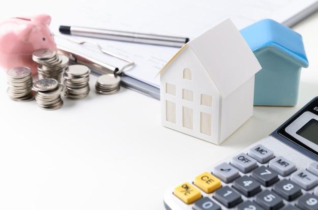 Modelo de casa de papel con moneda y hucha