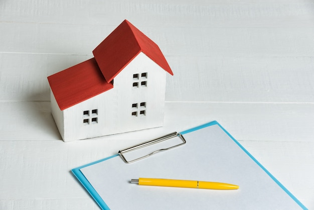 Modelo de casa, papeles y calculadora. compra de concepto de hipoteca de la casa.