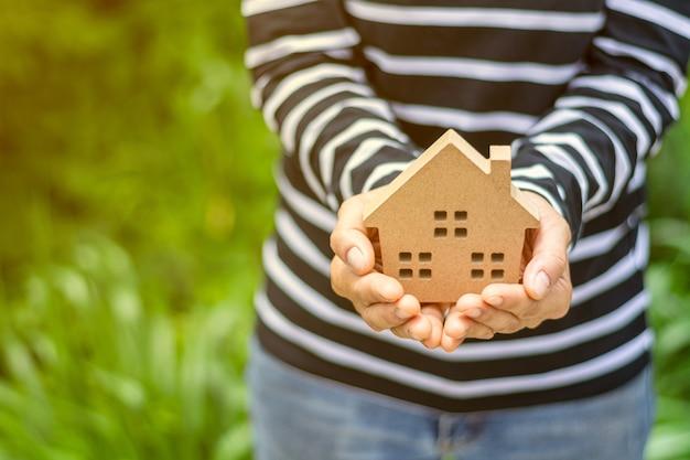 Modelo de casa pequeña en mano de mujer.