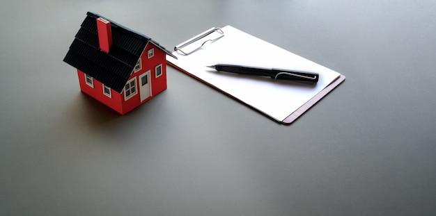 Modelo de casa pequeña con papel y bolígrafo.
