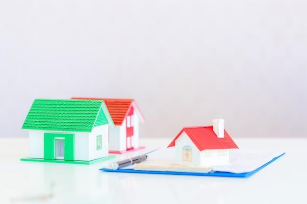Modelo de casa pintada de blanco bajo el techo de tejas sobre blanco.
