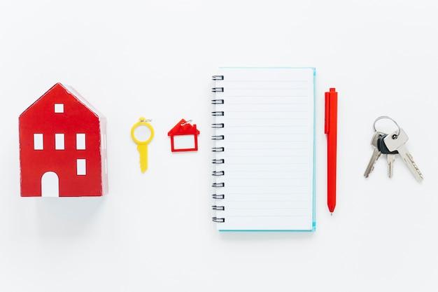 Modelo de casa roja; llave de plástico llavero en forma de casa; diario en espiral; pluma y llaves dispuestas en una fila sobre fondo blanco