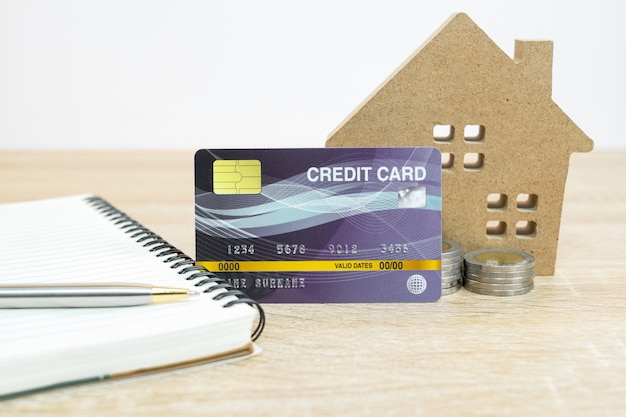 Modelo de casa y tarjeta de crédito en la mesa con bloc de notas para concepto de banca y finanzas