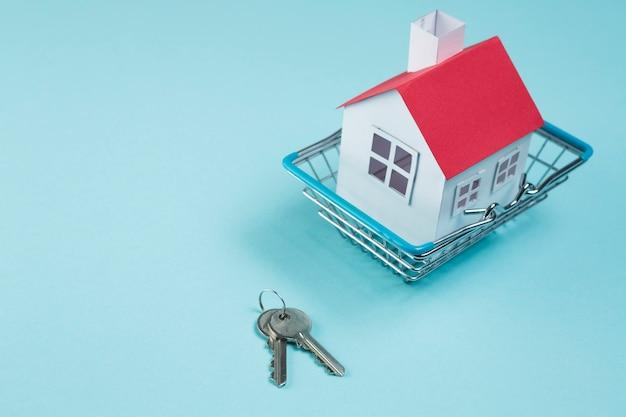 Modelo de casa de techo rojo en canasta metálica con llaves sobre superficie azul