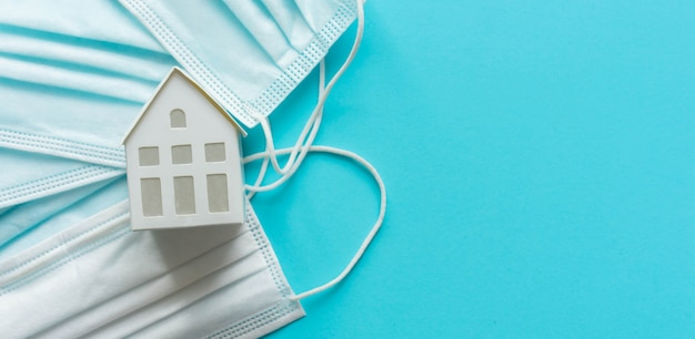 El modelo de la casa yacía sobre una mascarilla protectora sobre fondo de color azul para la cuarentena domiciliaria