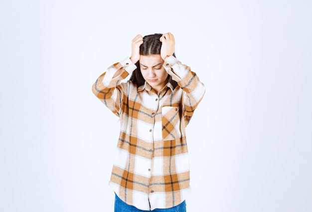 Modelo de chica joven irritada sosteniendo su cabeza y sufriendo de dolor.