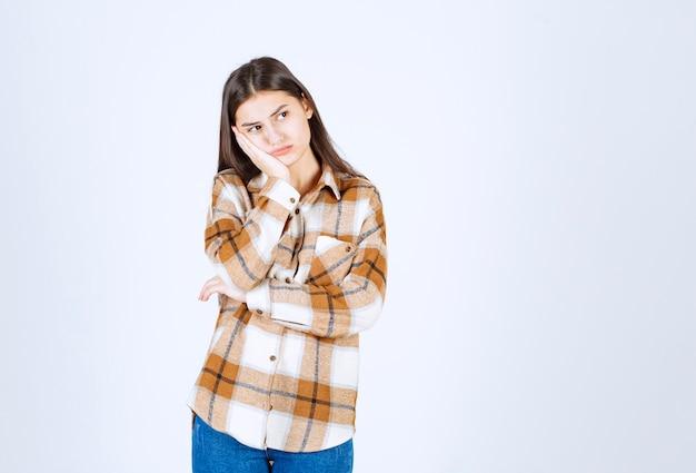 Modelo de chica joven pensativa de pie y mirando a otro lado.