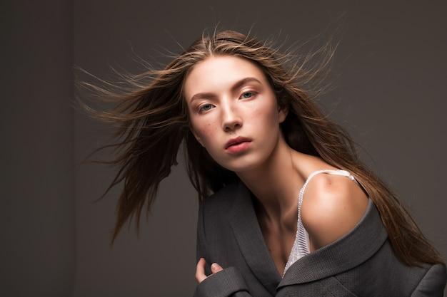Modelo de chica joven en traje de hombre gris de pie en studio