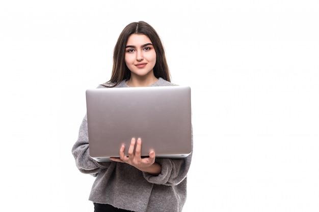 Modelo de chica morena en suéter gris de pie y estudio de trabajo en su computadora portátil