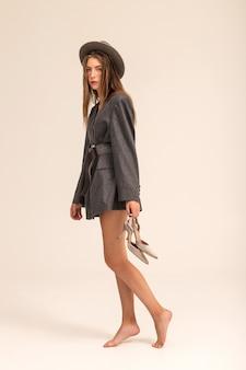 Modelo de chica rubia en chaqueta gris de gran tamaño y sombrero posando en studio