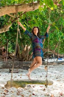 Modelo de chica sexy delgada en traje de baño posando en un columpio de madera atado a un árbol,