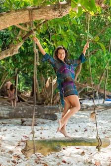 Modelo de chica sexy delgada en traje de baño posando en un columpio de madera atado a un árbol.