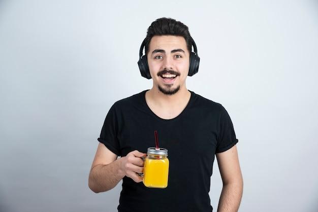 Modelo de chico guapo en auriculares sosteniendo un vaso con jugo de naranja.