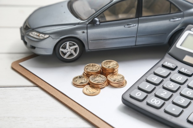 Modelo de coche, calculadora y monedas en la mesa blanca