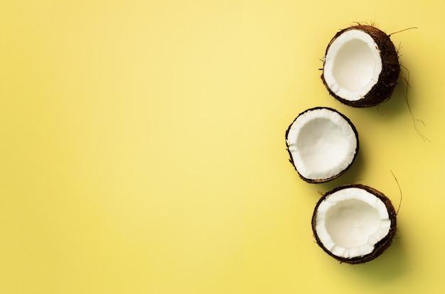 Modelo con los cocos maduros en fondo amarillo. diseño de arte pop, concepto creativo de verano. la mitad de coco en estilo minimalista.