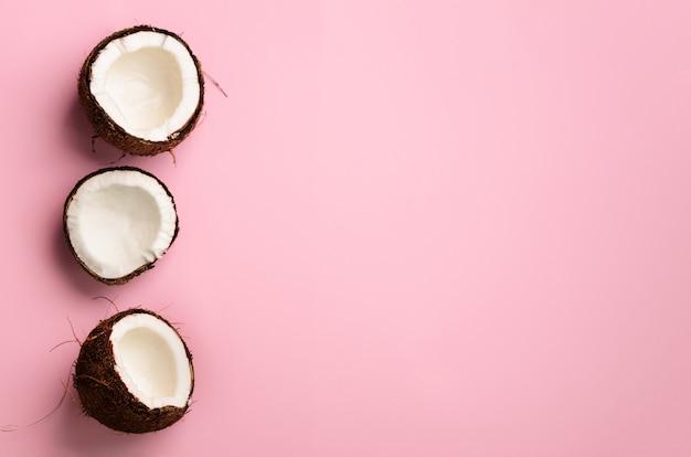 Modelo con los cocos maduros en fondo rosado. diseño de arte pop, concepto creativo de verano. la mitad de coco en estilo minimalista.