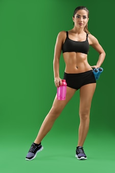 Modelo con cuerpo curvilíneo posando con botella de agua rosa.