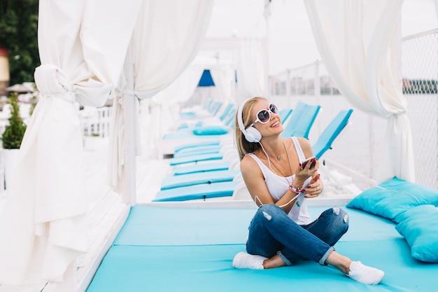 Modelo de contenido posando con auriculares en verano