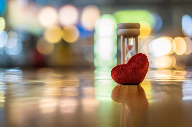 Modelo de corazón y reloj de arena en la mesa de madera, día de san valentín, amor y conceptos de tiempo.