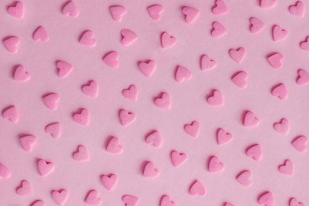 Modelo. corazones rosados de la confitería en el fondo rosado, textura