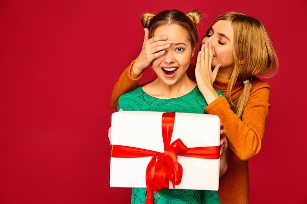 Modelo cubriendo los ojos de su amiga y dándole una gran caja de regalo y un secreto secreto