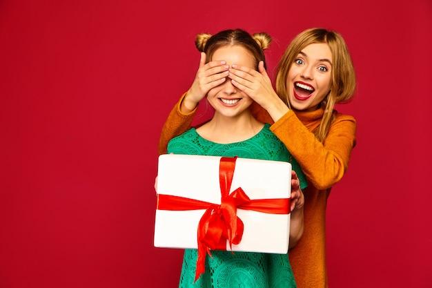 Modelo cubriéndole los ojos a su amiga y dándole una gran caja de regalo