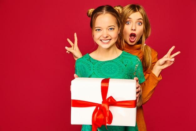 Modelo dando a su amiga una gran caja de regalo