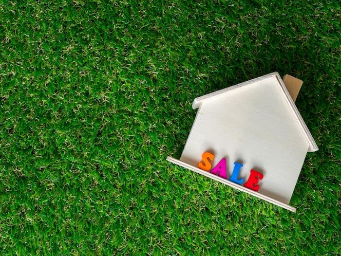 Modelo de casa de madera colocado en un césped verde y venta de texto colorido en la casa