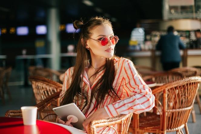 Modelo de moda bonito en gafas de sol rojos trabaja con su tableta sentado en el café