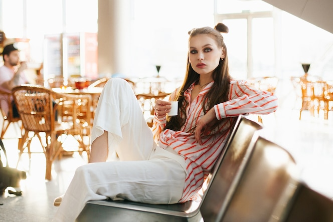 Modelo de moda joven se sienta con una taza de café en las sillas en el aeropuerto