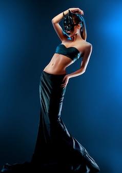 Modelo de moda magnífico que lleva la falda superior y larga negra y la máscara de batman