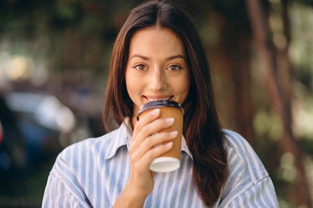 Modelo de mujer en camisa de hombre bebiendo café