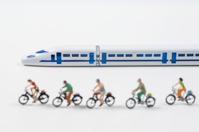Modelo de tren de alta velocidad y personas en miniatura montando una bicicleta