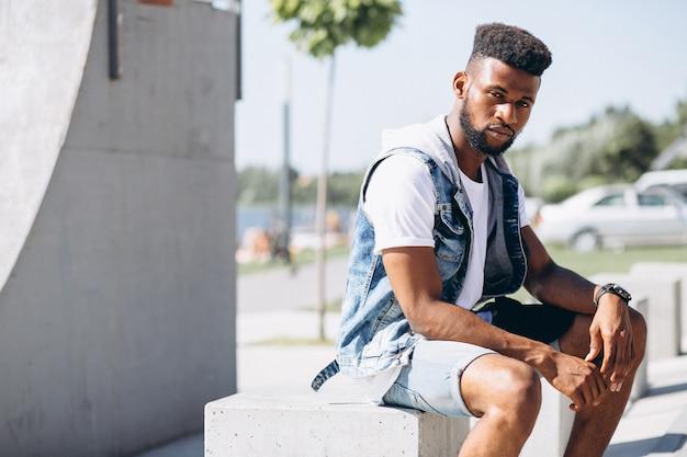 Modelo del hombre afroamericano que se sienta en parque en el fondo blanco