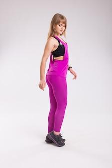 Modelo deportivo de fitness. vista de perfil lateral de mujer fitness en ropa de estilo deportivo.