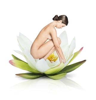 Modelo desnudo sobre una gran flor de loto