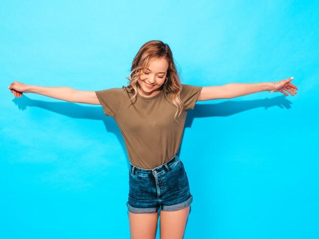 Modelo divertido que presenta cerca de la pared azul en estudio. levanta sus manos
