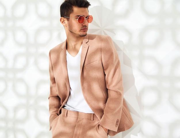 Modelo elegante vestido con elegante traje rosa claro posando junto a la pared blanca. metrosexual