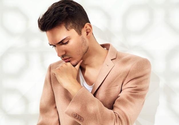 Modelo elegante vestido con elegante traje rosa claro posando junto a la pared blanca