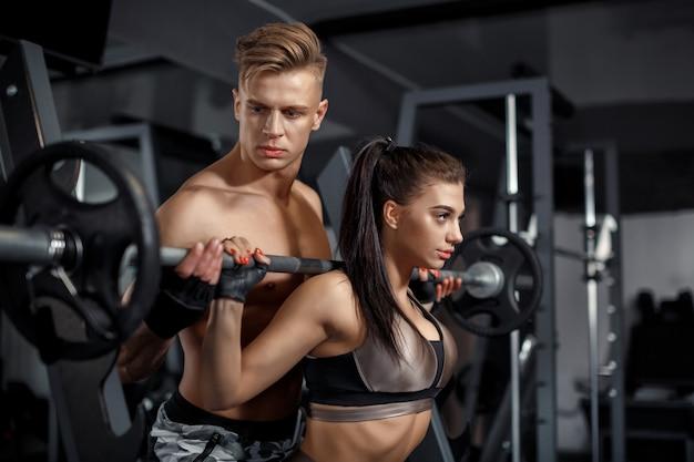 El modelo de entrenador personal ayuda a la mujer a levantar la barra en el gimnasio
