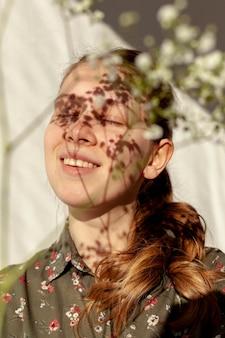Modelo feliz con flores desenfocadas