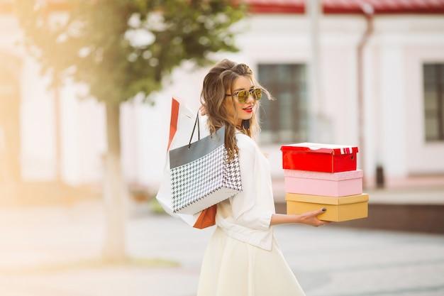 Modelo feliz en look blanco y gafas de sol con bolsas de compras u