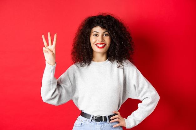 Modelo femenino alegre que muestra el número tres y sonriendo, haciendo un pedido, de pie en una sudadera sobre fondo rojo.