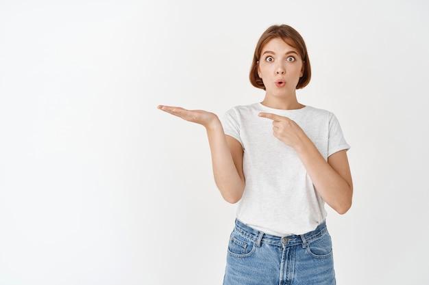 Modelo femenino asombrado sosteniendo el artículo en la palma, apuntando al espacio vacío de la mano como si mostrara el producto, publicidad en la pared blanca