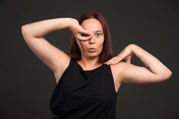 Modelo femenino en camisa negra haciendo pose de miedo.