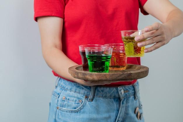 Modelo femenino en camisa roja sosteniendo una bandeja de bebidas.