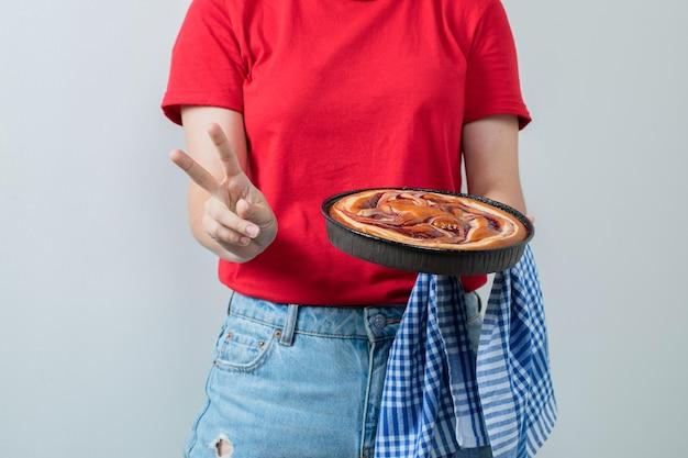 Modelo femenino en camisa roja sosteniendo un pastel dulce en una sartén negra.