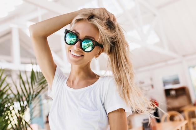 Modelo femenino en camiseta de moda y elegantes gafas de sol brillantes.